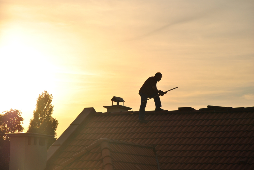 Man on a roof sunset | RoofingContractorPittsburgh.com