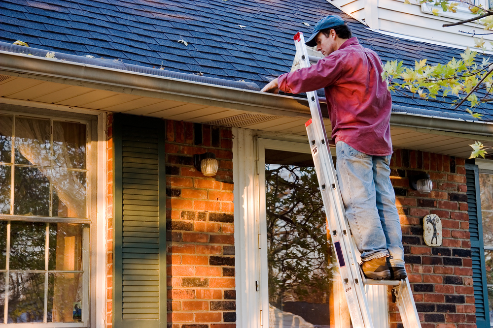 Man Cleaning His Gutters on Ladder | RoofingContractorPittsburgh.com