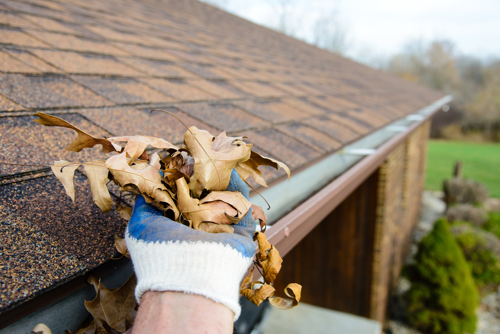 Man cleaning gutters of his home | RoofingContractorPittsburgh.com